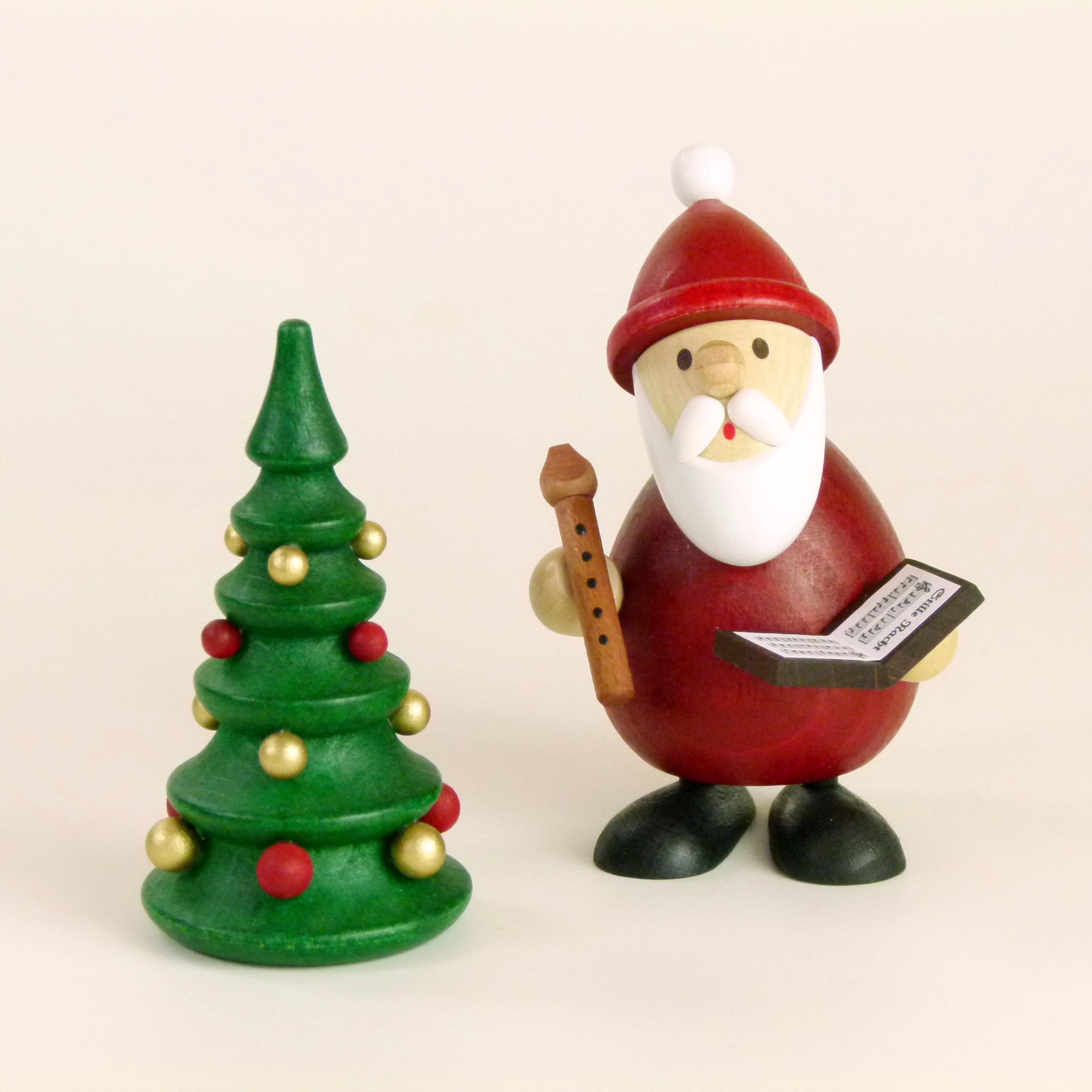 Weihnachtsmann mit Buch, Flöte und Weihnachtsbaum als weihnachtlicher Tischschmuck