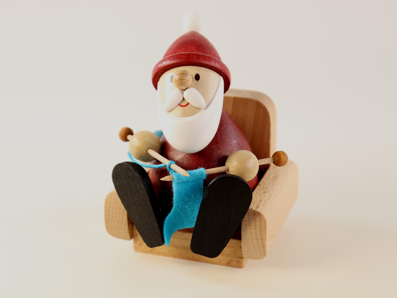 Weihnachtsmann im Sessel mit Stricknadeln als Tischschmuck