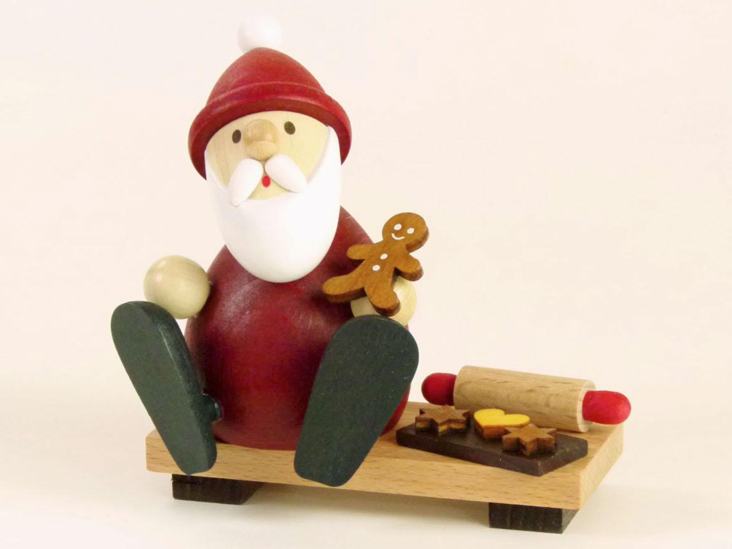 Tischschmuck: Weihnachtsmann modern auf Bank mit Lebkuchenmann, Backblech und Nudelholz